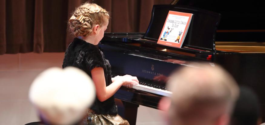 Young girl playing a piano in a recital